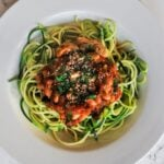 A top down view of a bowl of vegan puttanesca zoodles.
