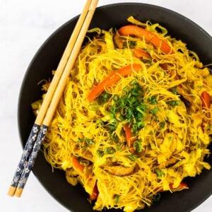 A close up view of a serving bowl of vegan Singapore noodles.