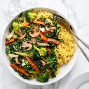 A close up view of a platter of vegetable chow mein with serving utensils in it.