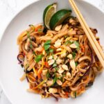 A top down view of a bowl of vegetable pad Thai with chopsticks resting on it.