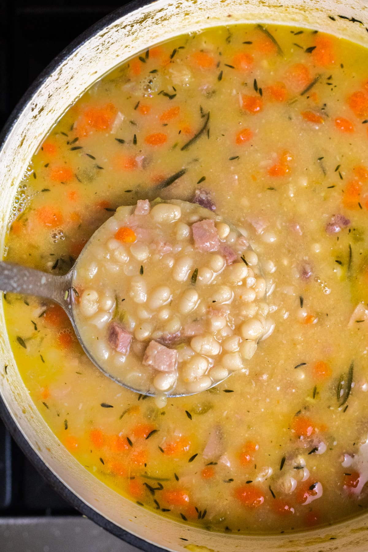 A top down view of cooked white bean and ham soup in a pot on the stove.