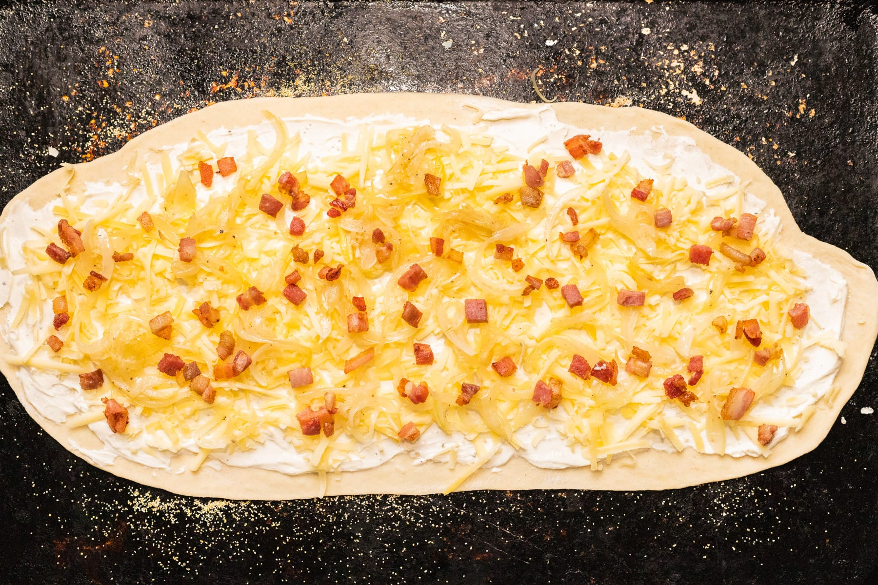 A top down view of unbaked flammkuchen on a baking sheet.