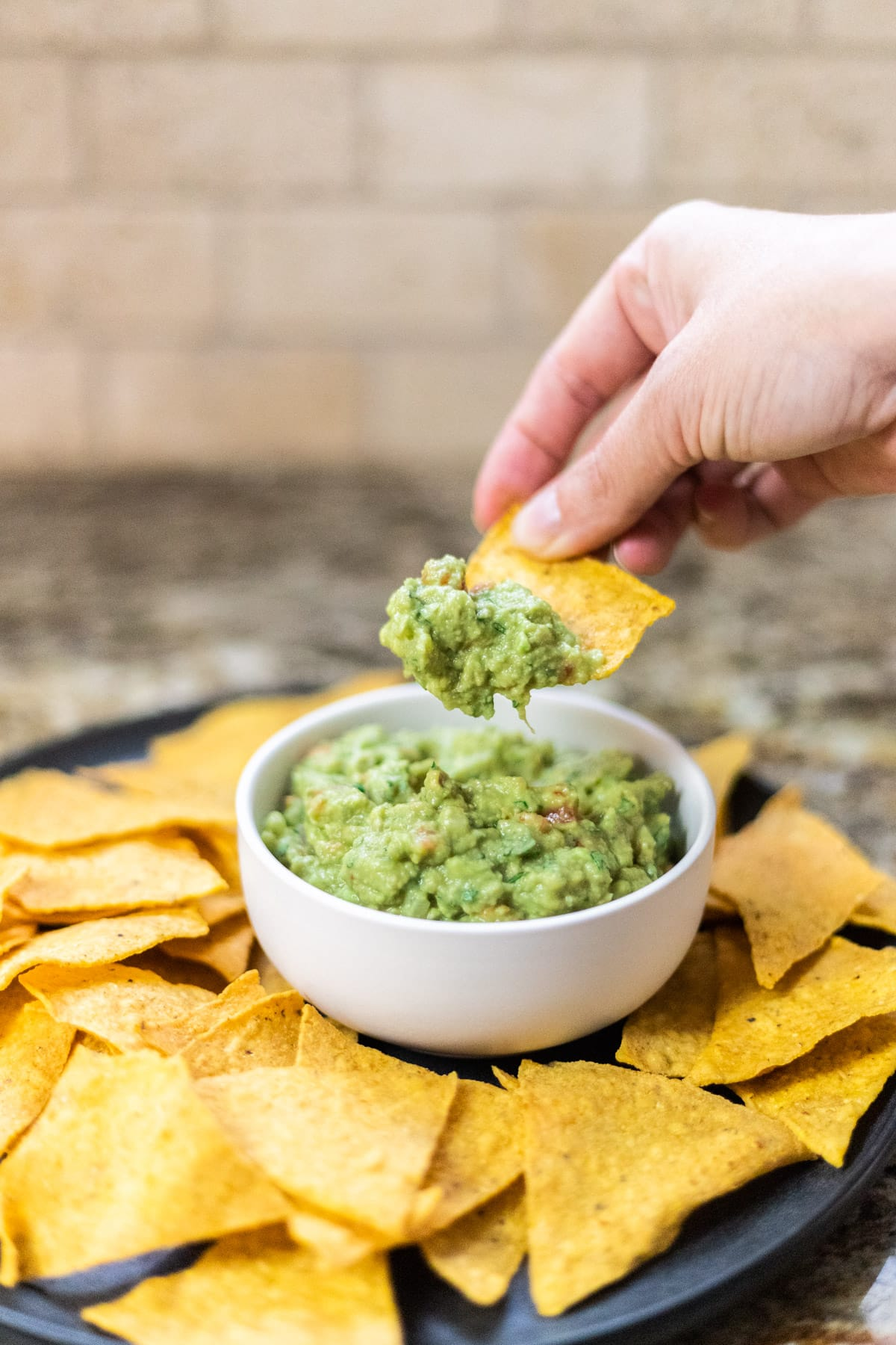A side view of a hand dipping a tortilla into a bowl of guacamole.