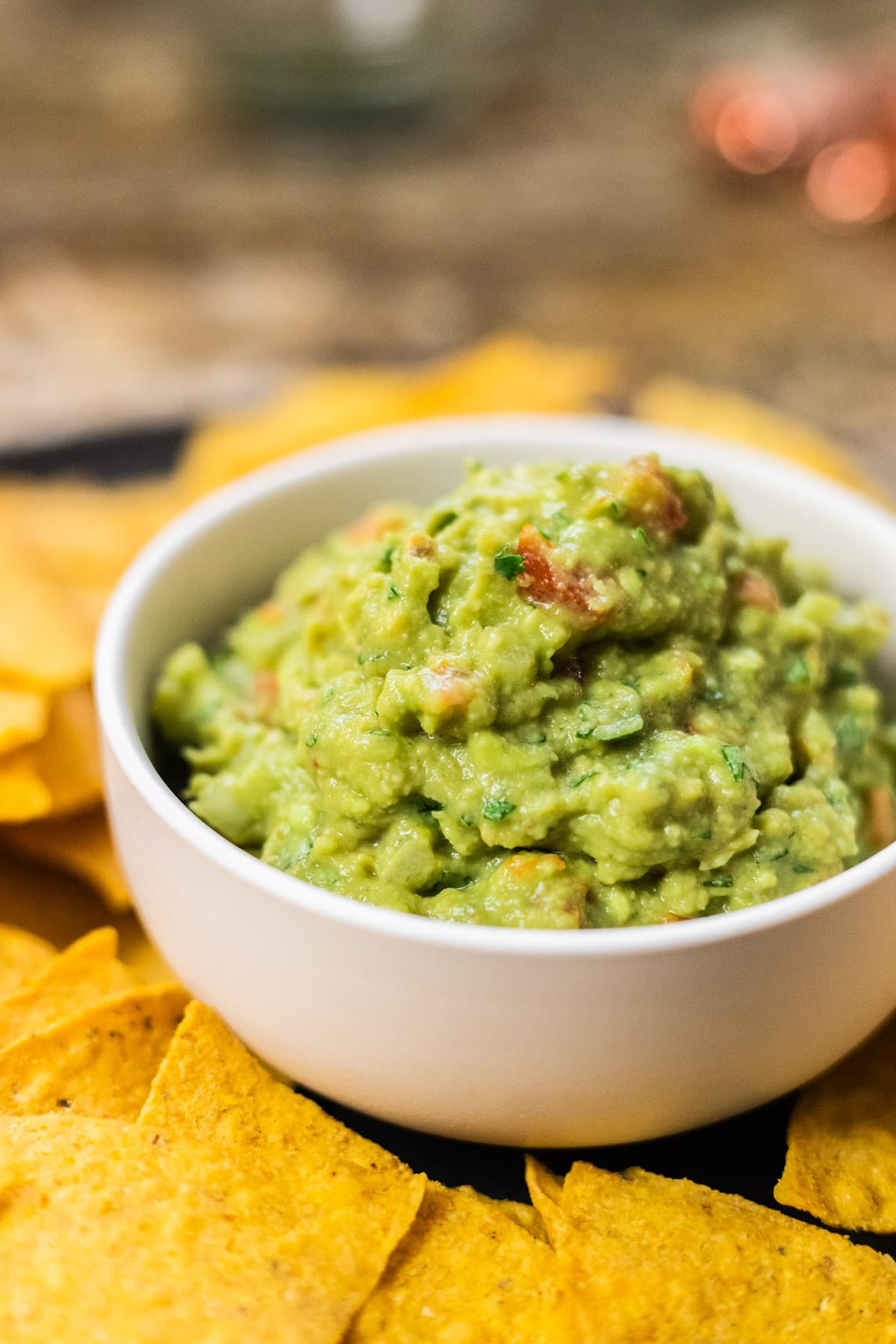 A side view of a bowl of guacamole surrounded by tortilla chips.