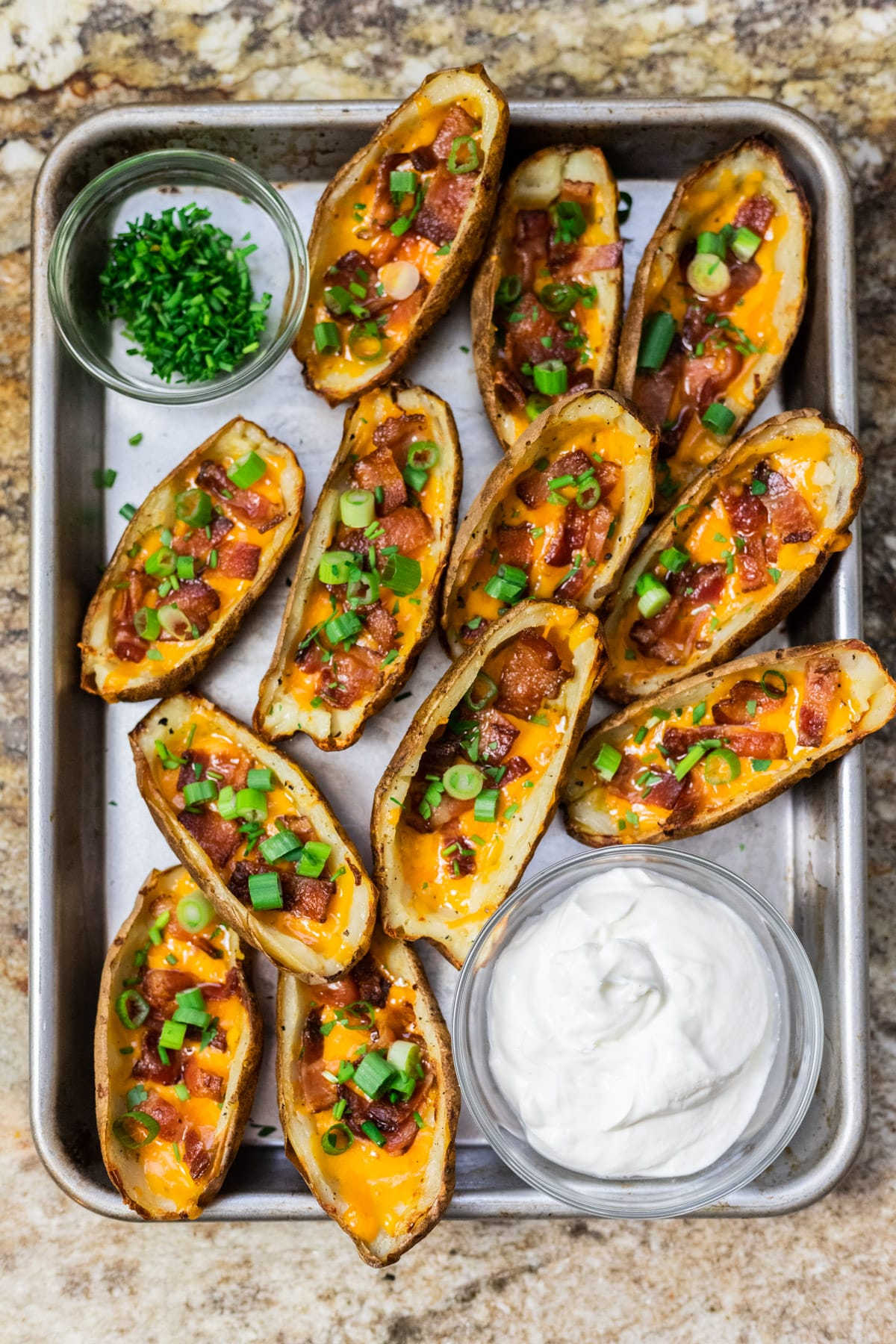 A top down view of loaded potato skins served on a tray with bowls of sour cream and chives.