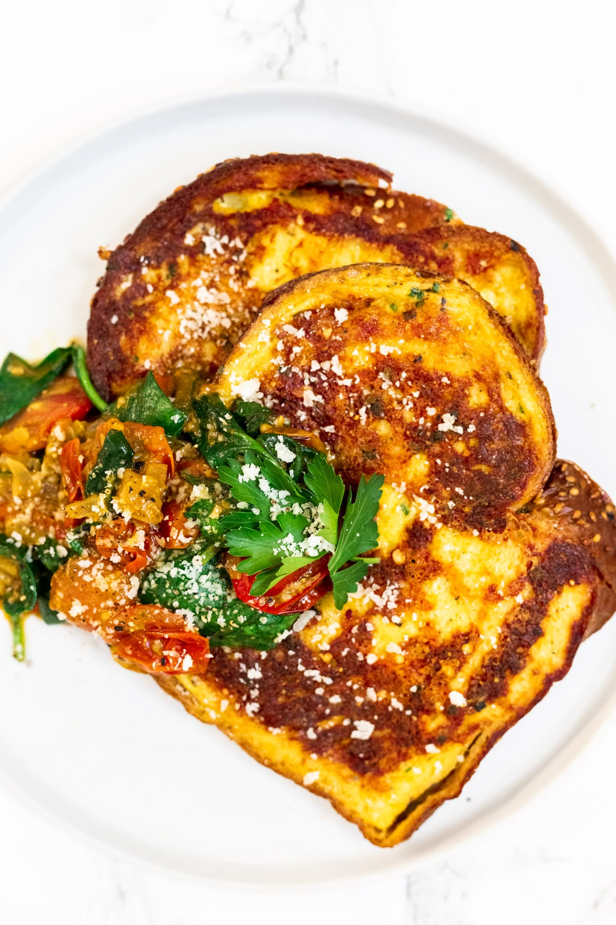 A close up view of a plate of savory parmesan crusted French toast served with pesto cherry tomato sauce.