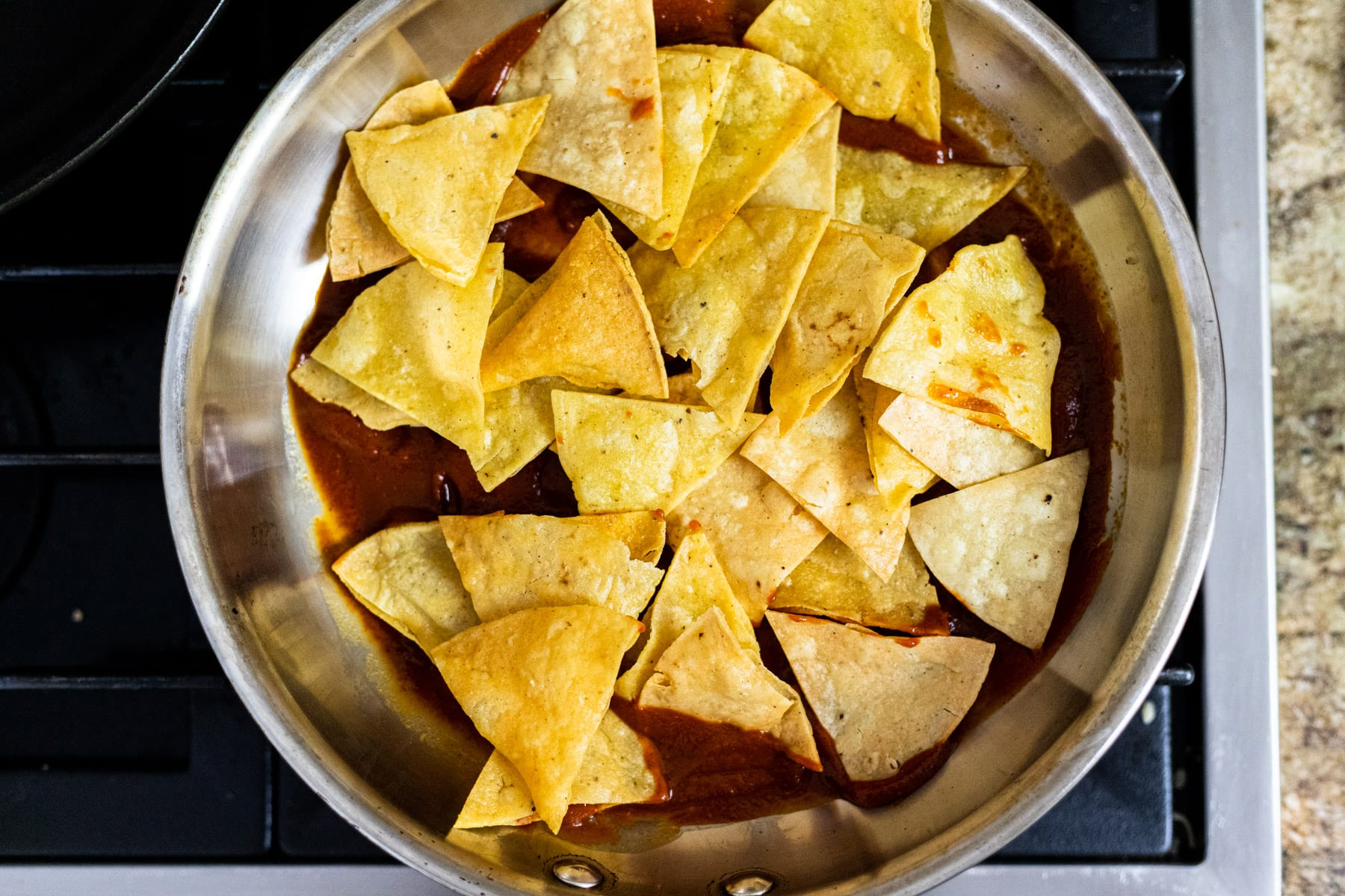 Tortilla chips on top of red chili sauce in a skillet.