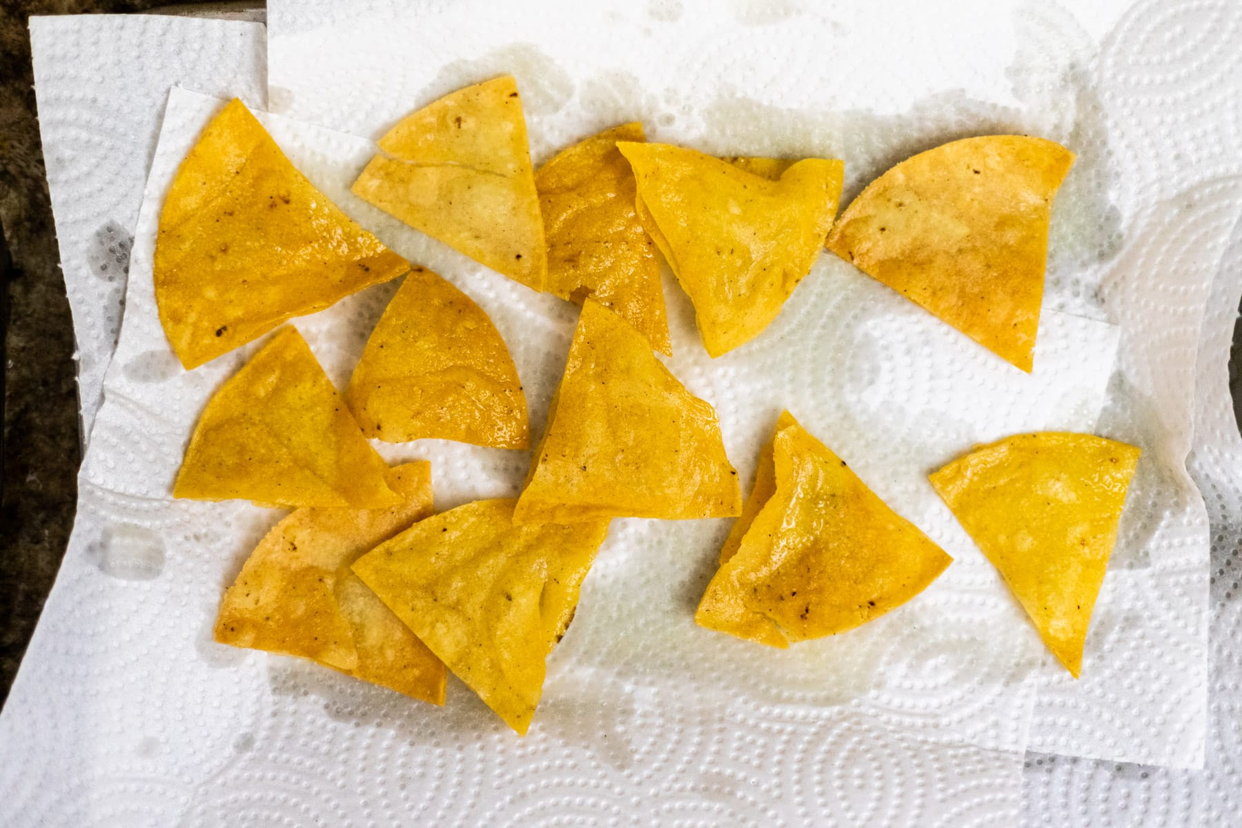 Corn tortilla chips resting on paper towel.