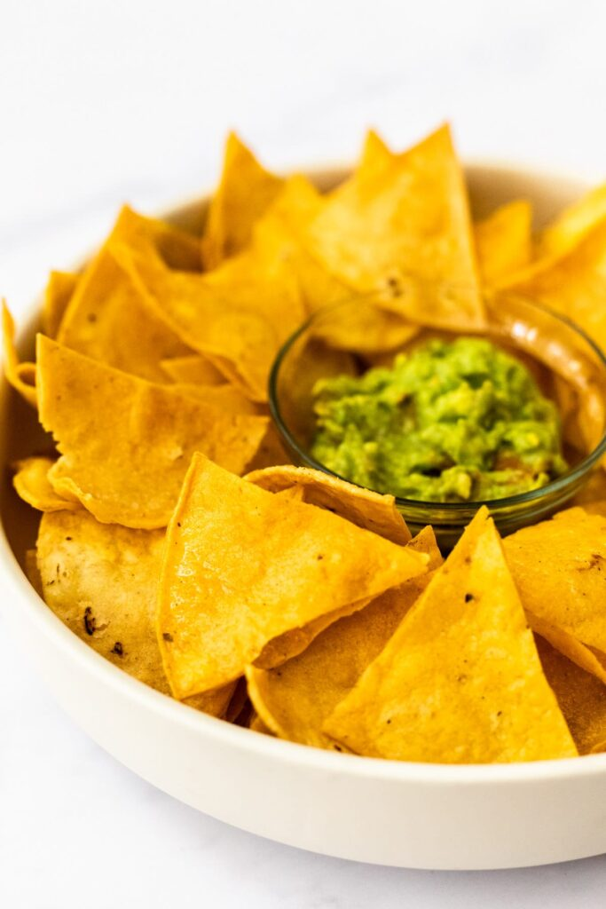 a side view of a bowl of tortilla chips with guacamole.