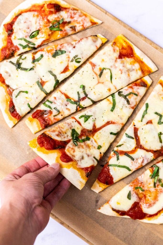 A hand grabbing slice of flatbread pizza