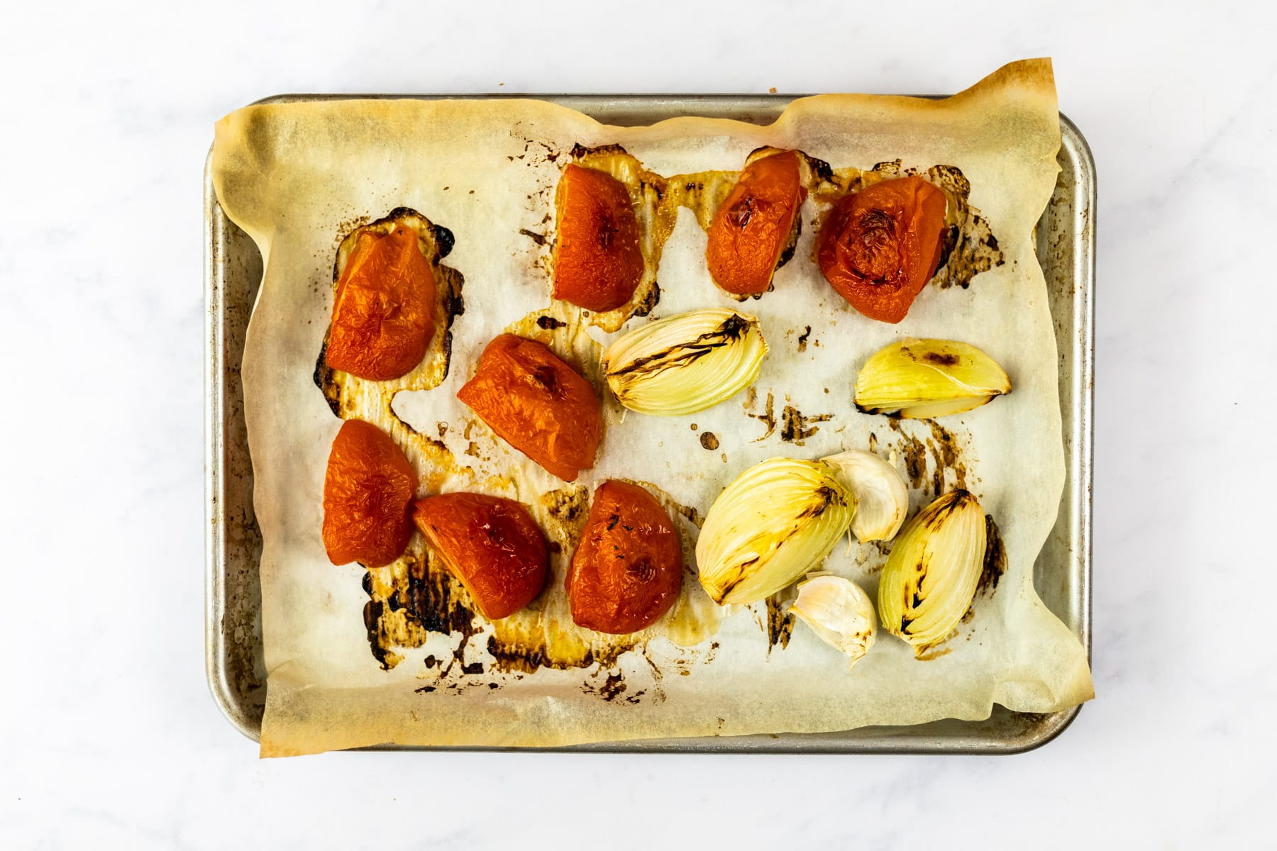 Roasted tomatoes, onion and garlic on a baking sheet.