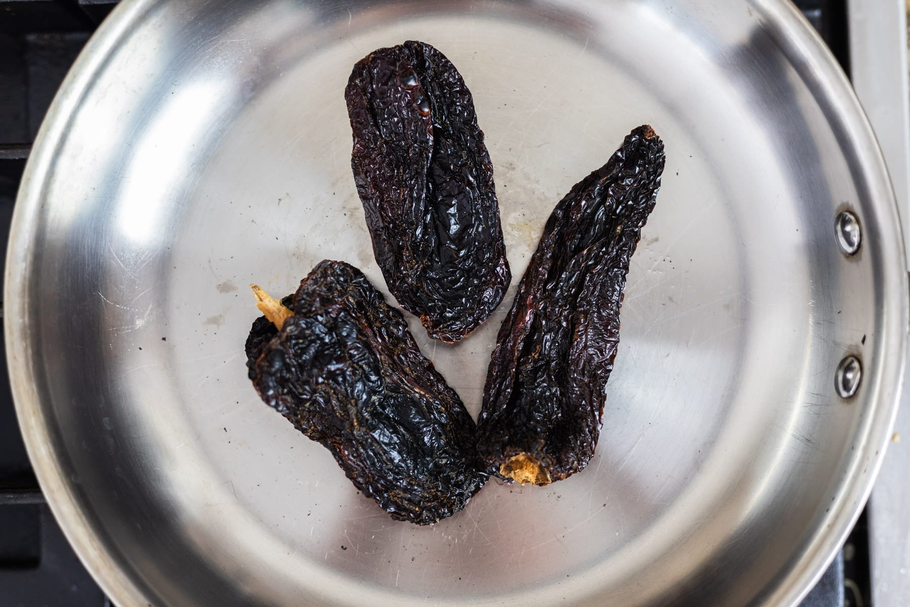 Toasted ancho chilis in a skillet.