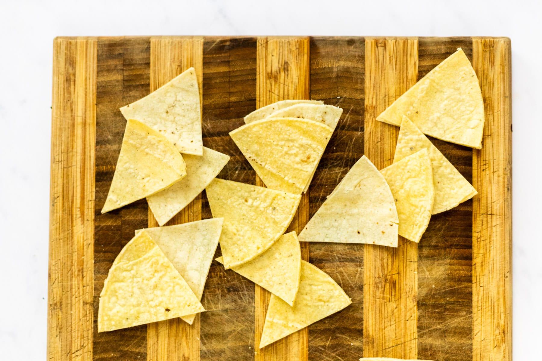corn tortillas cut into triangles on a cutting board.