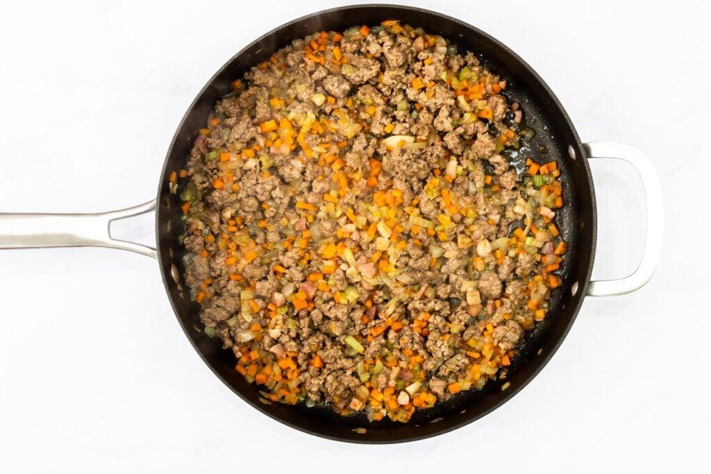 browned lamb and veggies in a saute pan