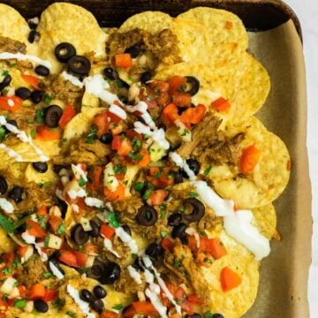 A close up view of pulled pork nachos on a sheet pan.