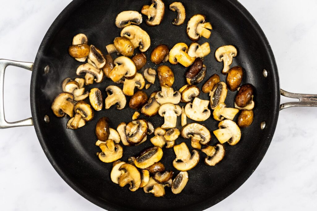 Mushrooms cooking in a skillet.