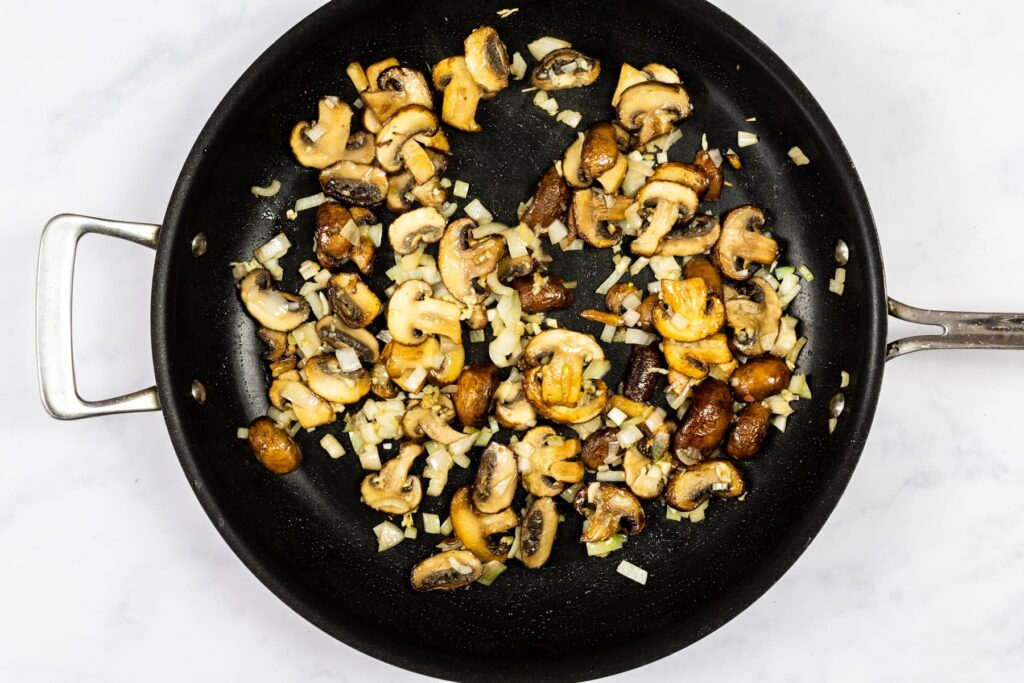 Mushrooms, shallots and garlic cooking in a skillet.
