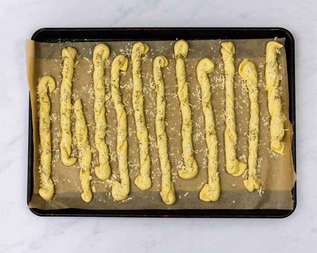 Breadsticks topped with garlic butter, parmesan cheese and seasonings on a baking sheet.