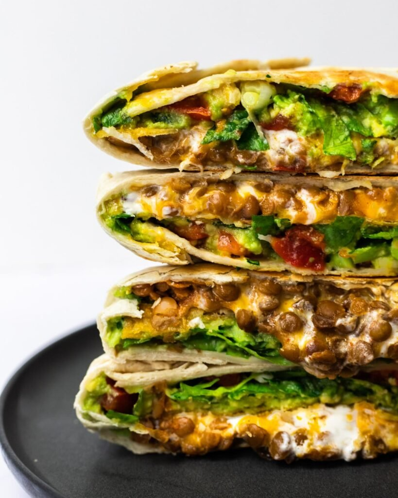 A side view of halved and stacked vegetarian crunchwrap supremes.