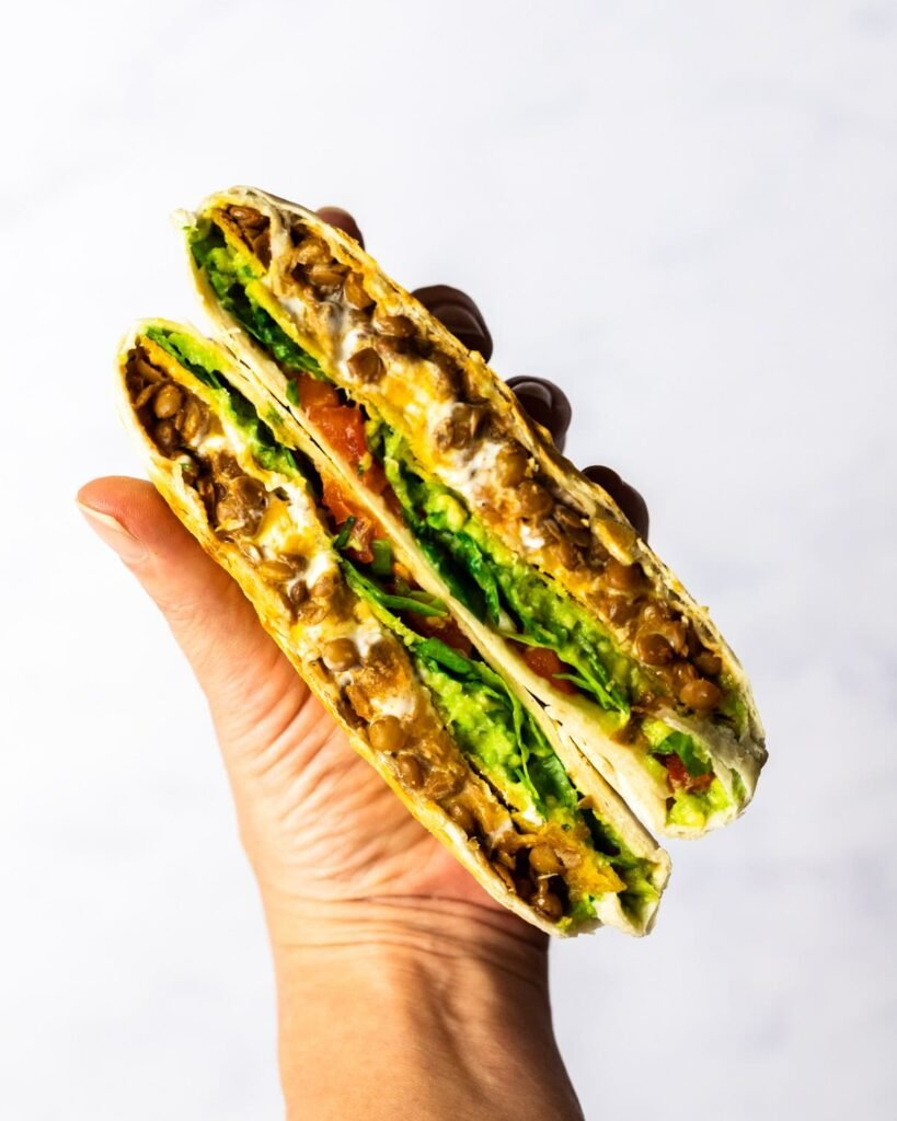 a hand holding up two halves of a vegetarian crunchwrap