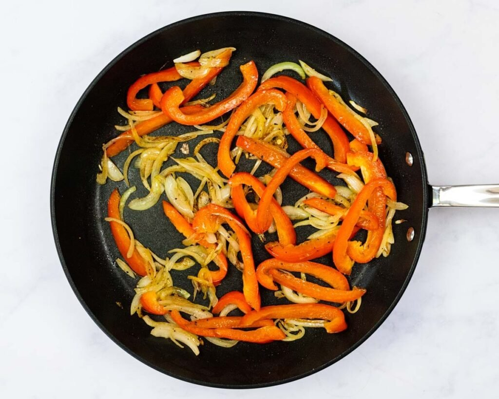 A top down view of sauteed peppers and onions in a skillet.