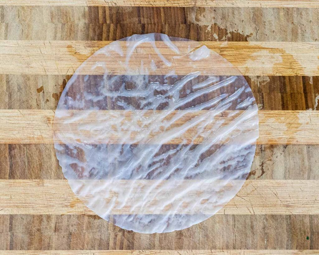 A soaked pice of rice paper on a cutting board.