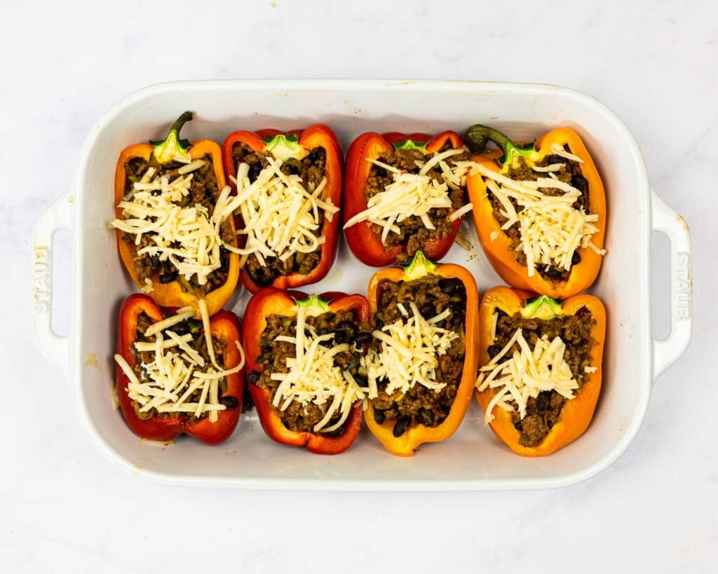 taco stuffed peppers in a baking dish before baking.