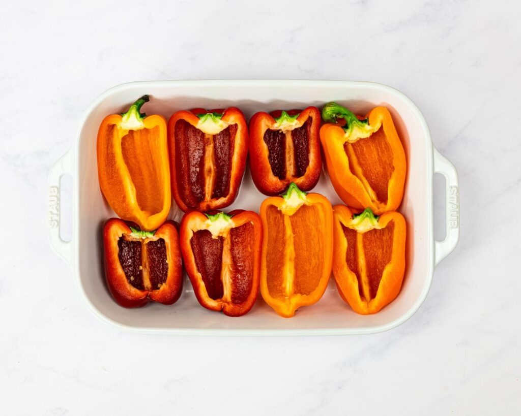 Halved peppers in a baking dish.