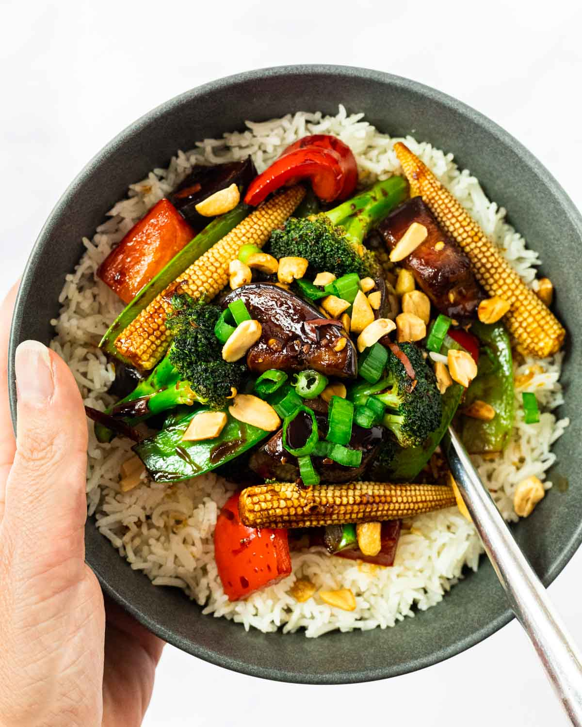 a hand holding a bowl of kung pao vegetables served over rice.