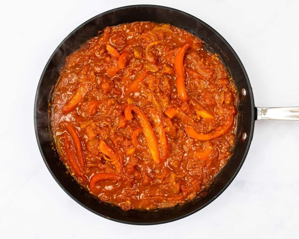 Reduced tomato sauce in a skillet.