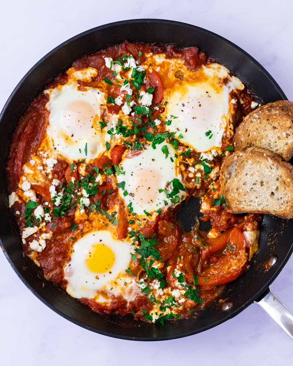 a top down view of a skillet of shakshouka with an egg missing.