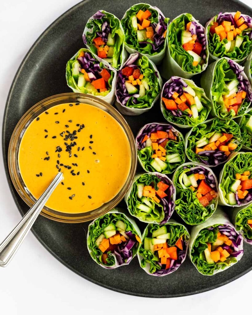 A top down view of a plate of veggie rolls with peanut dipping sauce on the side.
