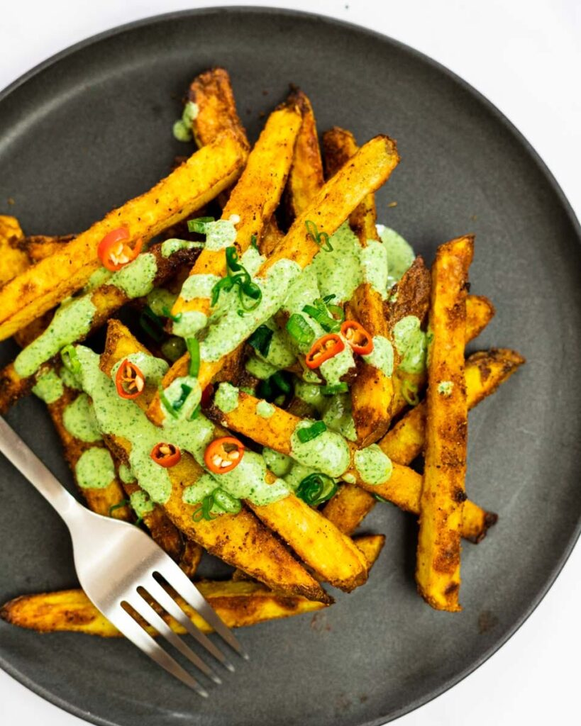 A top down view of a plate of masala fries drizzled with cilantro dipping sauce.