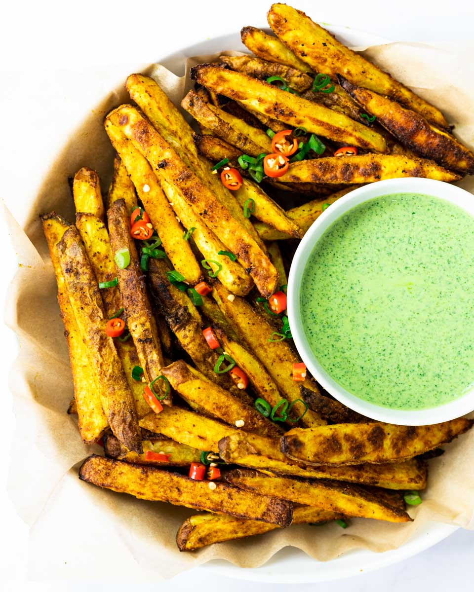 A top down view of a plate of masala fries with a side of cilantro dipping sauce.