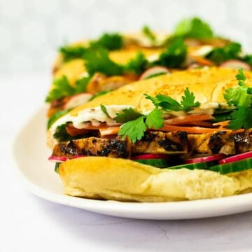 A side view of of a plate of grilled chicken banh mi sandwiches.