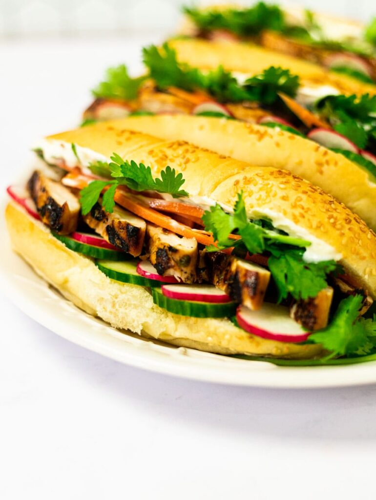 A side view of a plate of grilled chicken banh mi sandwiches.