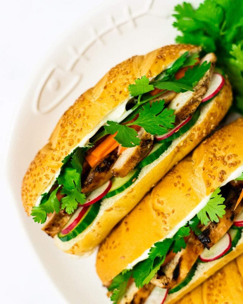 A top down view of a plate of grilled chicken banh mi sandiwches.