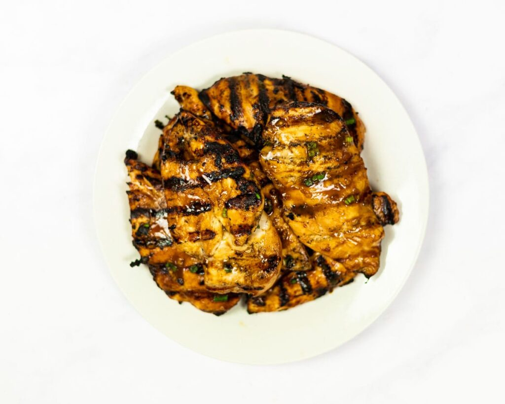 A top down view of grilled chicken on a plate.