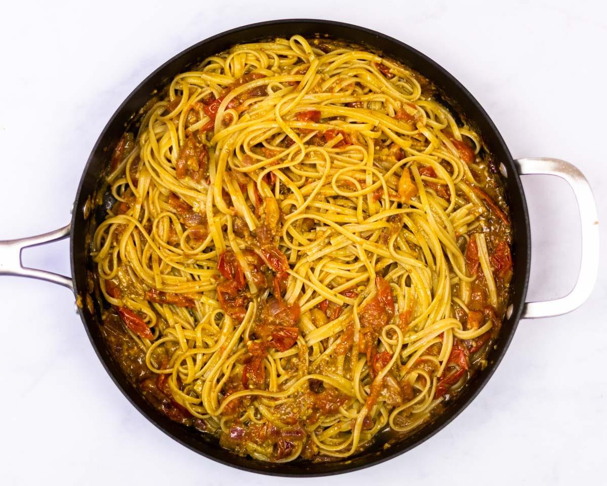 cherrry tomato pesto pasta in a saute pan.