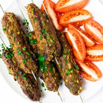A top down view of a plate of beef kofta kebabs.