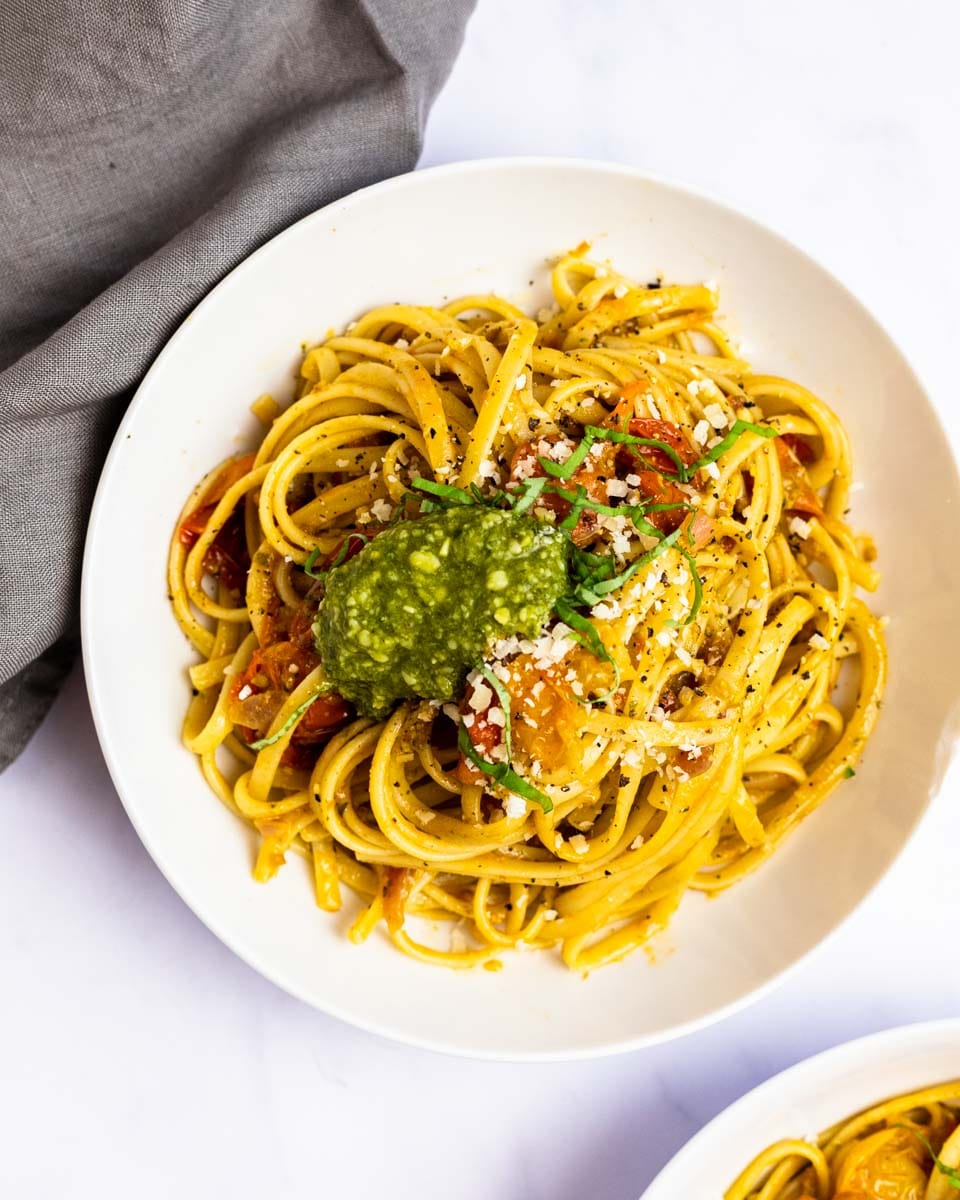 a top down view of a bowl of cherry tomato pesto pasta