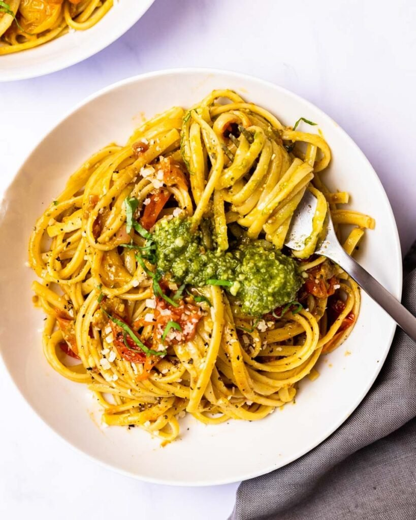 A top down view of a bowl of cherry tomato pesto pasta with a fork twirled in the noodles.