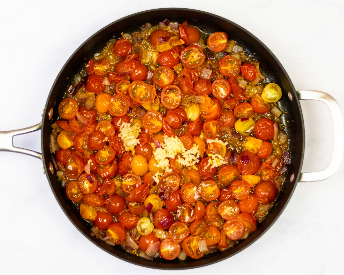 cherry tomatoes cooking in a saute pan with onion and garlic.