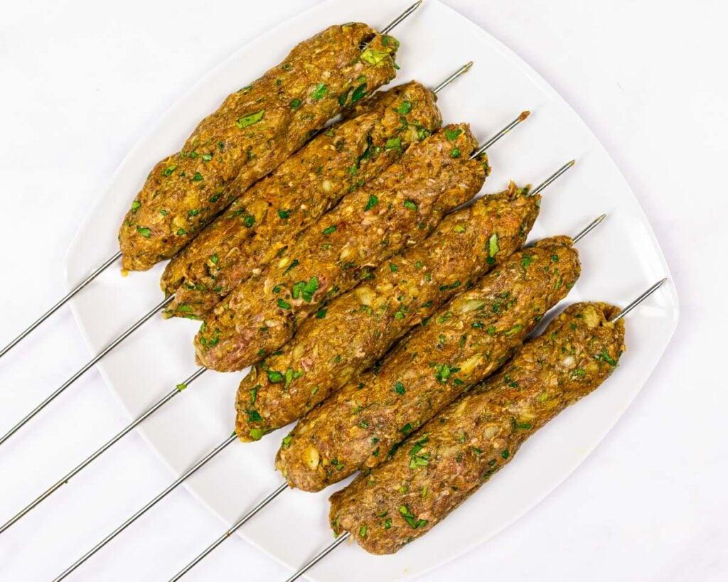 raw beef kofta kebabs on a plate